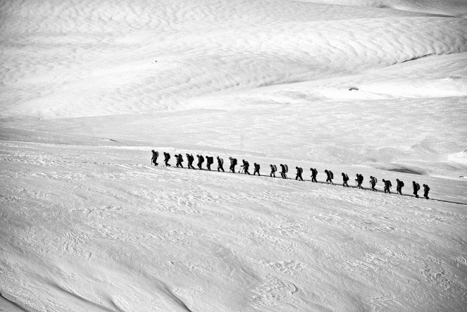 A long line of trekkers in the snow
